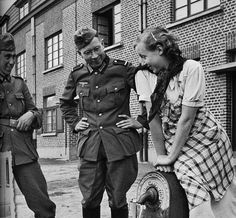 German soldiers flirting with a young maiden at a well. Paris, France