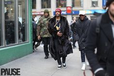 http://pausemag.co.uk/2016/02/street-style-special-aap-rocky-in-fur-coat-to-yeezy-season-3/   A$AP Rocky is another rapper who has embraced fashion. This was him on his way to the YEEZY Season 3 fashion show earlier this year.  Fur Coat. Red Skully. Two Gold Chains.  Graphic T.  Black Fitted Pants.  Black Vans.  He put street with luxury together, successfully.  Of course he's cool for that.