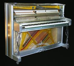 "A Gary Pons SY112 'Elegance' upright piano with an Altuglass and brushed, aluminium case. The transparent, Altuglass lid, fall and case front allows the instrument and action to be visible. This piano is from the show-stopping ""Plexart"" Collection, each one numbered and signed by their creator. With a variety of options on case styling each piano, is a unique, luxurious, artistic creation. This piano is available to order at Besbrode Pianos"