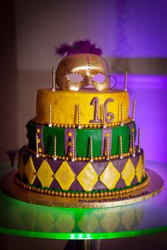 Uplighting and DJ by GueProductions, color-changing glow-in-the-dark cake table changing between the theme's colors (purple, gold, green), with the beautiful custom birthday cake and custom Mardi Gras mask cake topper by Angelic Affairs