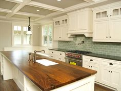Wood countertops for island. White kitchen, gray ceiling, and a surprising muted color for subway tiles. Great blend!