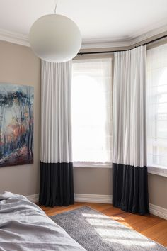 A beautiful example of deep hemmed drapery, high contrast, ripples fold on a decorative rod in a bay window! Bay window, white linen, charcoal grey, chocolate curtains, drapes,