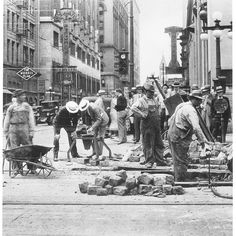 Street Repair Crew, Corner of 6th Avenue and Locust looking North, late 1920's to early 30's. Bankers Trust bldg. is behind the traffic light. St. Ambrose Cathedral is distance