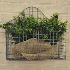 "Ideal for any part of your home, this wall basket fits right in with any farmhouse or country cottage decor. Organize magazines to eliminate clutter or add color and beauty to your decor with faux greens or flowers.  Cottage Wire Wall Basket Galvanized wire 14""H x 15""W x 5""D"