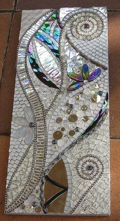 Love it!  Notice the subtle use of the silver ball chain to create definition and texture.  Fantastic! Please note that the link will take you to Mosaic Tile Mania, a mosaic supplier, not the art work itself.
