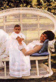 Audrey Hepburn photographed with her son Luca by Henry Clarke at La Paisible, her house in Tolochenaz, Switzerland, in February 1971. Audrey wears a Valentino gown (haute couture, all white, made of tulle and point d'esprit embroidery with Oriental pearls, created especially for her in February 1969).