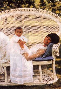 """Audrey Hepburn Dotti fotografiado con su hijo Luca por Henry Clarke en su famoso """"La Paisible"""" en Tolochenaz (Suiza), en febrero de 1971.  -Audrey llevaba un vestido de noche de Valentino (alta costura, todo blanco, hecho de tul y punto bordado con perlas orientales, creado especialmente para ella en febrero de 1969 d'esprit)."""