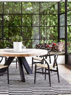 Amazing windows and lovely contrasting round dining table with great chairs