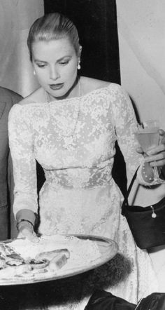 1955 Grace Kelly plays hostess.at the Cannes Film Festival in her Cassini lace gown, part of his 1954 collection