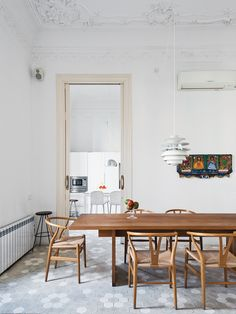 In the dining room, a Poul Henningsen lamp hovers over a table by Philipp Mainzer for E15, surrounded by Hans Wegner Wishbone chairs.