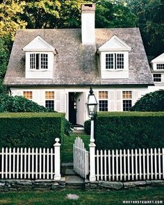 Charming house ~  Love the white picket fence, the lamp post, the shutters on the windows and the off centre chimney.
