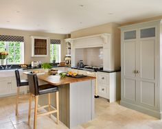 photo of bespoke farmhouse traditional cream harvey jones kitchen with breakfast bar and aga bar stools plate rack