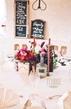 Ódon esküvői dekoráció piros árnyalatú virágokkal, régi tárgyakkal és gyertyákkal | old wedding decoration with shades of red flowers, old things and candles