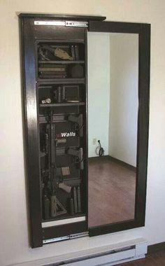 Hidden safe/storage behind mirror. Ok, so I don't have a bunch of guns to hide - but this would be so cool.....