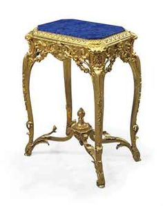 A LOUIS-PHILIPPE ORMOLU AND LAPIS-LAZULI GUERIDON  MID-19TH CENTURY  The later canted rectangular lapis-lazuli veneered top within a fleur-de-lys surround, above a pierced foliate rocaille frieze centred to front and back by cupids flanking interlaced L's, on cabriole legs headed by fleur-de-lys filled shells running to scrolled feet, and joined by an 'X'-shaped stretcher centred by an urn with pomegranate finial  30¼ in. (77 cm.) high; 21½ in. (55 cm.) wide; 16 in. (40.5 cm.) deep