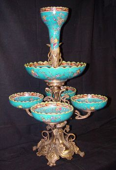 porcelain and bronze epergne. An epergne is a type of table centerpiece, usually made of silver, but may be made of any metal or glass or porcelain. source Wikipedia