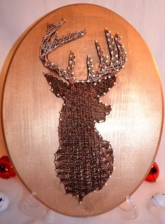 - This shimmery oval wooden plaque holds a reindeer silhouette made of all different shades of string from gold to brown. - With both rose gold and silver nails every aspect of this piece compliments