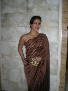 Kajol, in a Amit Agarwal sari, uses a Malaga El Dorado clutch to great effect in this look!