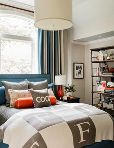 Gray and blue boy's bedroom features a blue nailhead bed dressed in gray and…