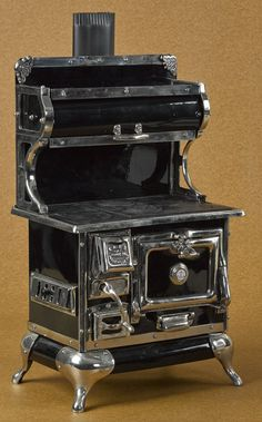 Reproduction Karr Range Co. enameled, iron, and tin toy cook stove with a black surface and nickel trim, 21'' h., 12 1/2'' w.