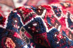 Detalle de alfombra Shiraz. Alfombra persa por excelencia, anudadas a mano por tribus nómadas con lana 100% obtenida de sus propios rebaños. Con predominio de color rojo y motivos geométricos. #alfombra #persa #shiraz #rojo #decoración