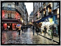 Latin Quarter - Paris, France.  Love the rain and the reflected lights & umbrellas.  Processed in my iPhone using Snapseed App