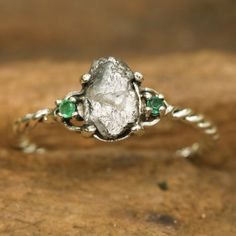 Natural rough diamond ring with tiny emerald side set gems in prongs setting with sterling silver oxidized twist design band