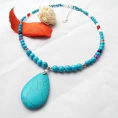 Handmade Turquoise Statement Necklace on sale now - Only £20. Stunning statement necklace with various size Turquoise gemstone beads offest with white shell beads and red/purple glass crackle beads. Lovely Turquoise centrepiece (aprox 50mm). -
