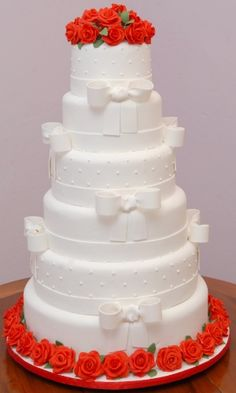 Bolo de seis andares com textura de poás e decorado com laços brancos e flores vermelhas; da Fabiola & Liana - Cake Shop (www.fabiolaeliana.com.br), a partir de R$ 260. Disponibilidade e preço pesquisados em dezembro de 2013 e sujeitos a alteração