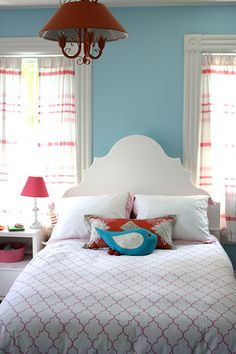 "Sneak Peek: A Massachusetts Farmhouse Where Color and Pattern Meet. ""Our daughter who lives in this room is an elegant girl who gravitates towards a feminine style, so I think this room really reflects her personality.  We painted this vintage light fixture orange from black to complement the orange and pink that the room features.  The walls are painted Morning Glory blue by Benjamin Moore."" #sneakpeek"