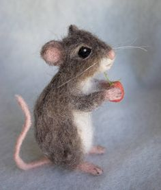 A whimsical, yet realistic grey brown mouse created of wool and alpaca. This little mouse has a wire frame which allows him to be posed and his hands can hold small things. He is about 4 inches tall. He is perfect for adding to your home decor display and a string can easily be added