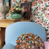 un coussin réalisé avec plein de fleurs en croche de toutes les couleurs cousues sur un fond en lin rond comme housse, posé sur un fauteuil bleu pastel dans un esprit anglais.