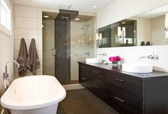 #Contemporary and elegant bathroom design with dark #wood and glass #shower doors