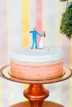 Brides.com: . A one-tier white-and-pink wedding cake topped with modern bride and groom figurines, created by Flying Apron.