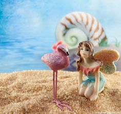 Our mini rainbow fairy poses with a flamingo at the fairy garden beach.