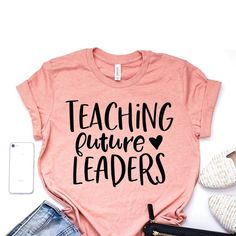 A super cute Teaching Future Leaders shirt that is a perfect gift for teacher appreciation. A great shirt for the teacher in your life to wear to class. Makes for a great set of shirts for a teaching team to wear to show off to the rest of the teachers. Teaching Shirts, Teaching Outfits, Preschool Teacher Shirts, Teacher T Shirts, Teacher Clothes, T Shirts For Teachers, Teacher Tattoos, Teacher Wardrobe, Teachers Pet