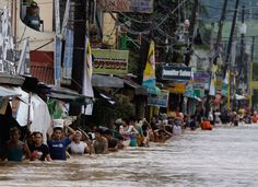 Residents cross a flooded road in Marikina City, east of Manila, Philippines, on August (AP Photo/Aaron Favila) Philippine Holidays, Monsoon Rain, Weather And Climate, Manila Philippines, Purple Rain, Red Cross, Natural Disasters, Rainy Days, At Least