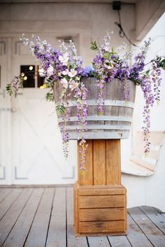 Rustic purple wildflowers with wine barrel and wood boxes / http://www.deerpearlflowers.com/another-20-rustic-wine-barrels-wedding-decor-ideas/