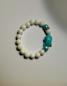 Classic White beads finished with Blue Buddha charm, Tiffany blue beads and rhinestone spacer bead.  This is a perfect addition to most any wardrobe ... elegant and simple. The beautiful beads are strung on stretchy elastic and so very easy to wear. This bracelet is approximately 7 ¼ inches