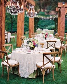 Wooden beams, crystal chandeliers, and cane chairs with cushions create an inviting outdoor room