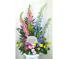 """Garden arrangement with keepsake memorial stone ideal for funeral visitations and services. """"To everything there is a season, and a time to every purpose under Heaven. Ecclesiastes 3:1"""" Arrangement is designed using pink snapdragons, blue delphinium, iris, and accent flowers in pink, purple, and yellow. Arrangement measures approximately: 25""""h x 16""""w Sympathy Funeral Keepsake Gift"""