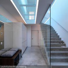 Die Treppe aus Beton sorgt für modernes Design-Flair und ist das Statement des Eingangsbereiches. Durch den Deckenabschnitt aus Glas fällt auch in den unteren Bereich des Hauses das Licht aus dem Oberfenster der Etage darüber. So lässt sich zusäzliche Beleuchtung einsparen.