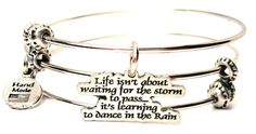 """Life Isn't About Waiting For The Storm To Pass It's Learning To Dance In The Rain Triple Style Bracelet. Get the style of wearing three bangles with only buying one bracelet. Charm is 100% Genuine American pewter. Will arrive in a gift box. ChubbyChicoCharms exclusive design expands to over 8"""". Hand Made in the USA."""