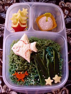 Little angel fish tuna sandwich is swimming in colored Top Ramen with a carrot crab and apple starfish. Smaller compartments are filled with...