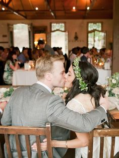 Frantic taps on guest wedding glasses equals a cute kissing moment! Capture a smooch at dinner for a candid wedding reception shot.