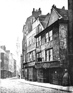 """Old houses and shops in Drury Lane, London, c1890s. The """"Cock and Magpie"""" Inn, from earlier in the century, has vanished from the premises on the right"""