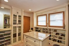 Decorative molding & fluted columns add elegant texture to this walk-in closet, while a mirrored cabinet door doubles as a vanity.  Learn more here: https://www.closetfactory.com/custom-closets/ Closet Island, Fluted Columns, Decorative Mouldings, Custom Closets, Dressing Rooms, Custom Cabinetry, Big Closets, Crown Molding, Laundry Rooms