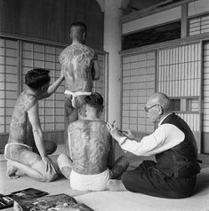 1946, Tokyo, Japan ~ A Japanese tattoo artist works on a group of  Yakuza gang members. ~ Image by © Horace Bristol