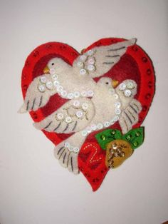 Completely hand-sewn, this ornament is part of the 12 Days of Christmas set. The heart, with the turtle doves, hangs 5 and is 4.5 at its widest