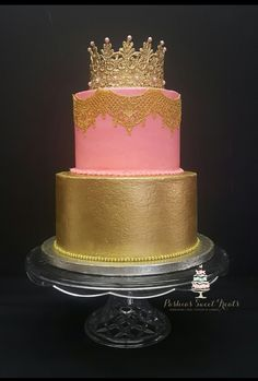 """Made this cake for a wonderful customer today. This two tiered cake is a 6"""" vanilla cake with pink buttercream icing with an edible gold lace. The bottom is a 8"""" vanilla cake with buttercream icing painted with an edible gold color. The crown on top is made from lace with some pink pearls on it."""
